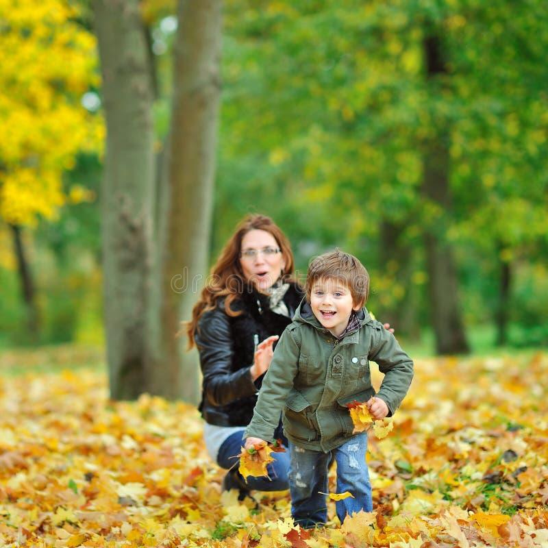 Barnet kör i väg från moder, medan plaing i en park arkivfoton
