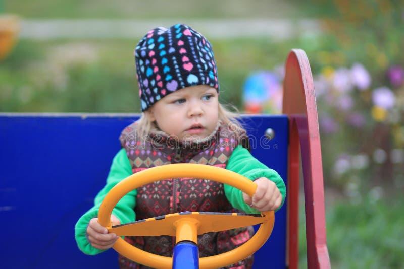 Barnet kör träbilen på dagislekplatsen royaltyfri foto