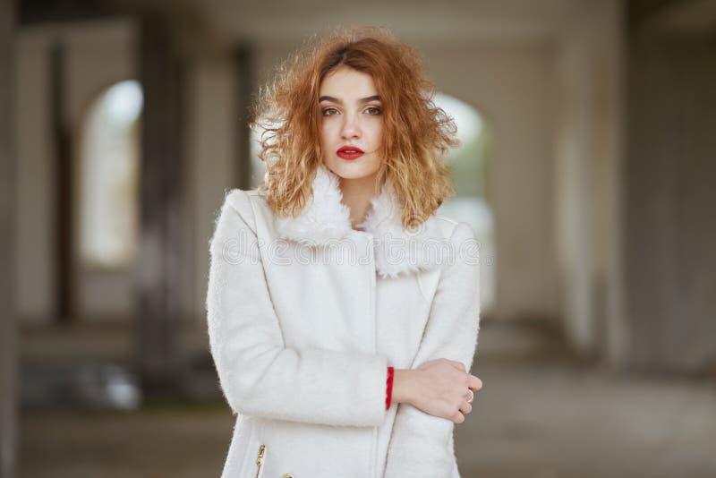 Barnet klädde fashionably den rödhåriga flickan med lockigt hår i vitt posera för lag som ser kameran i ett övergett rum fotografering för bildbyråer