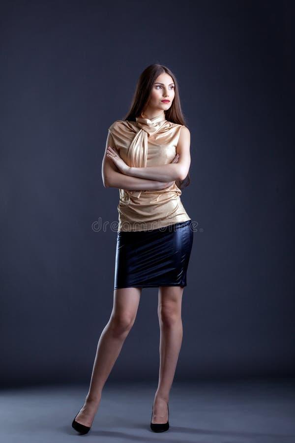 Barnet klädde stylishly kvinnan som poserar i studio fotografering för bildbyråer