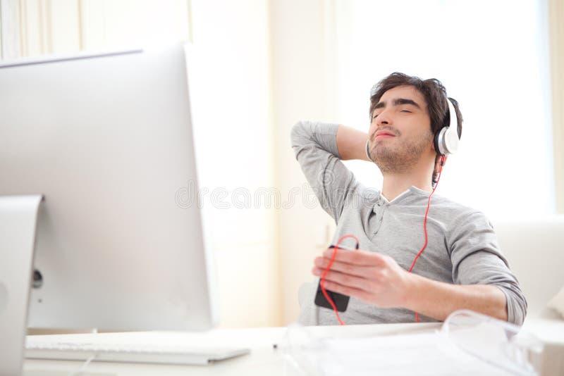 Barnet kopplade av listenning musik för man på kontoret arkivbild