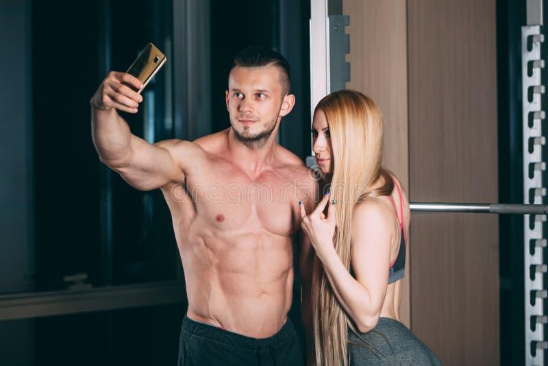 Barnet kopplar ihop att öva i idrottshall med viktmannen, selfie, kort på telefonen royaltyfri fotografi