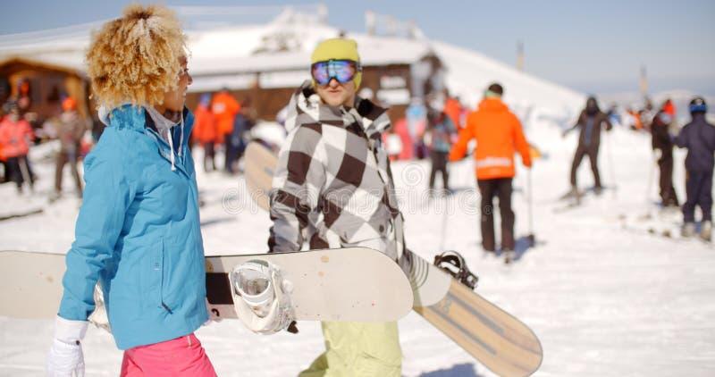Barnet kopplar ihop att bära deras snowboards på en semesterort arkivbilder