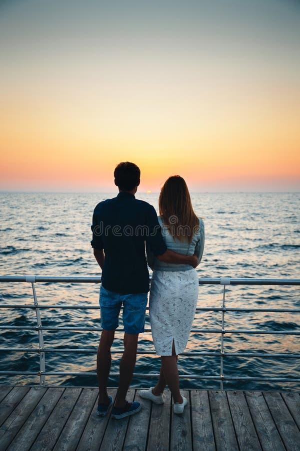 Barnet kopplar ihop att hålla ögonen på soluppgången på stranden, baksidasikten, kustsommarstrand på havet för horisonten för gul royaltyfri bild
