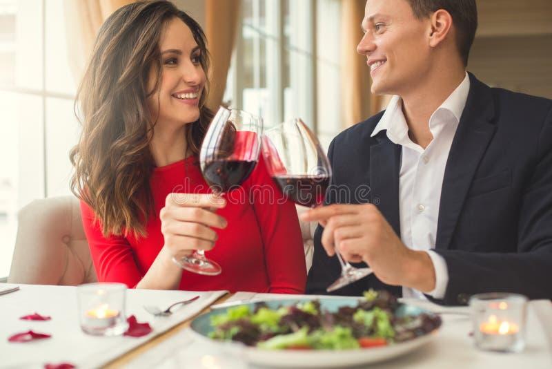 Barnet kopplar ihop att ha den romantiska matställen i restaurangen som sitter rymma tillsammans främre sikt för vinexponeringsgl fotografering för bildbyråer