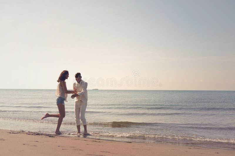 Barnet kopplar ihop att ha gyckel på en sandig kust royaltyfri fotografi