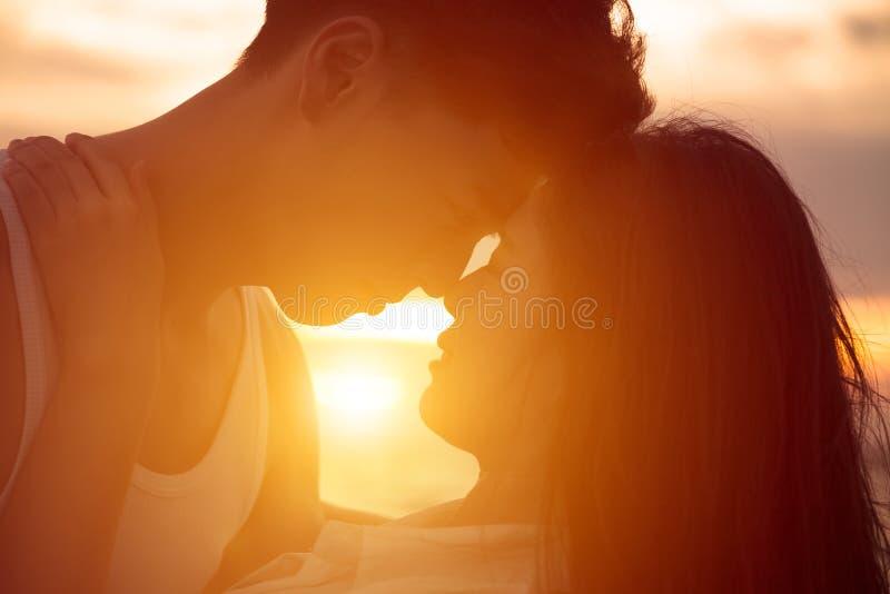 Barnet kopplar ihop att kyssa på solnedgången arkivbild