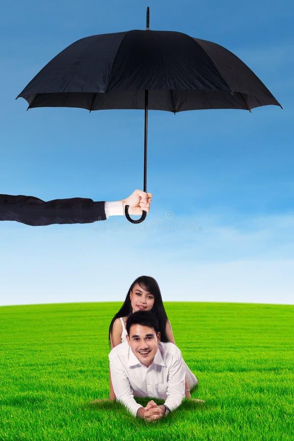Barnet kopplar ihop att ligga på gräset under paraplyet royaltyfri bild