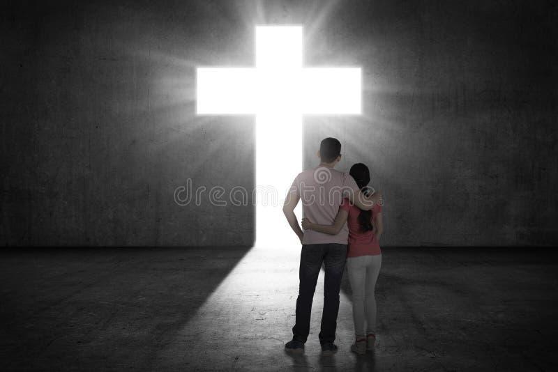 Barnet kopplar ihop att se det glänsande korset på väggen royaltyfri fotografi