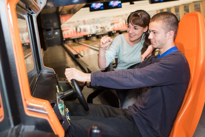 Barnet kopplar ihop att spela videospelet för körningshjulet i modigt rum royaltyfri bild