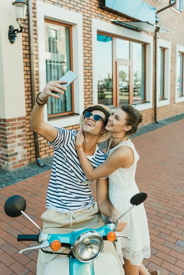 Barnet kopplar ihop att ta selfie på smartphonen, medan sitta på sparkcykeln utomhus arkivbilder