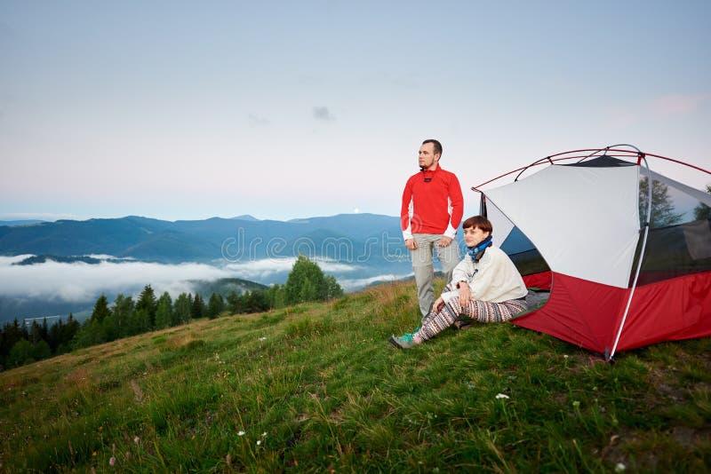 Barnet kopplar ihop att tycka om nära att campa i bergen fotografering för bildbyråer