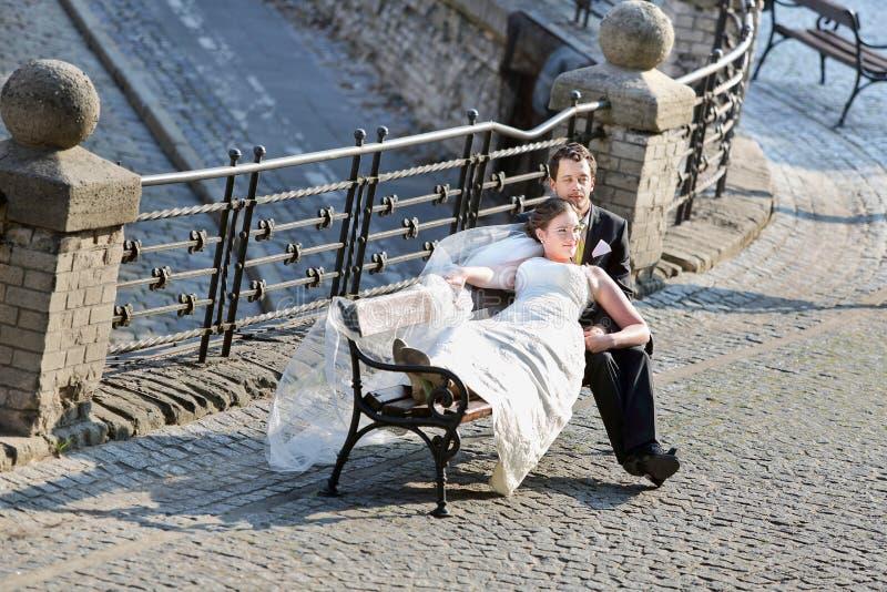 Barnet kopplar ihop att vila på bänken, når de har gifta sig fotografering för bildbyråer
