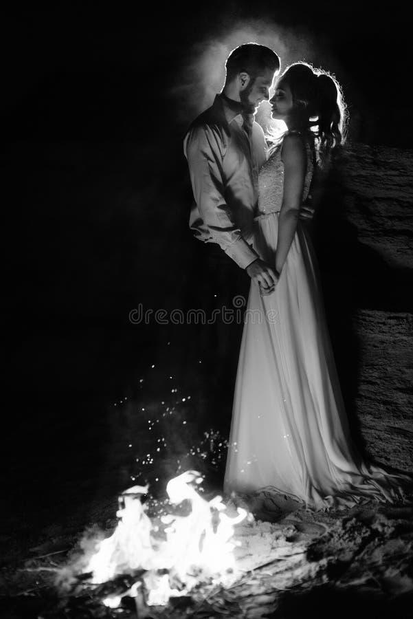 Barnet kopplar ihop bruden och brudgummen som är varma runt om branden royaltyfri foto