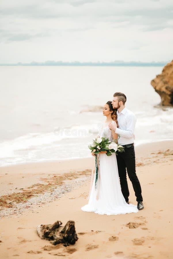 Barnet kopplar ihop brudgummen med bruden på en sandig strand fotografering för bildbyråer