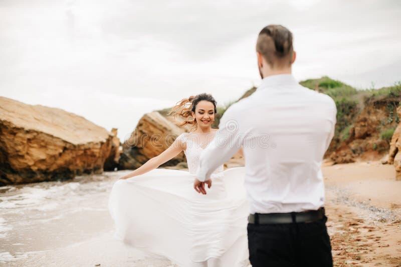 Barnet kopplar ihop brudgummen med bruden på en sandig strand arkivbilder