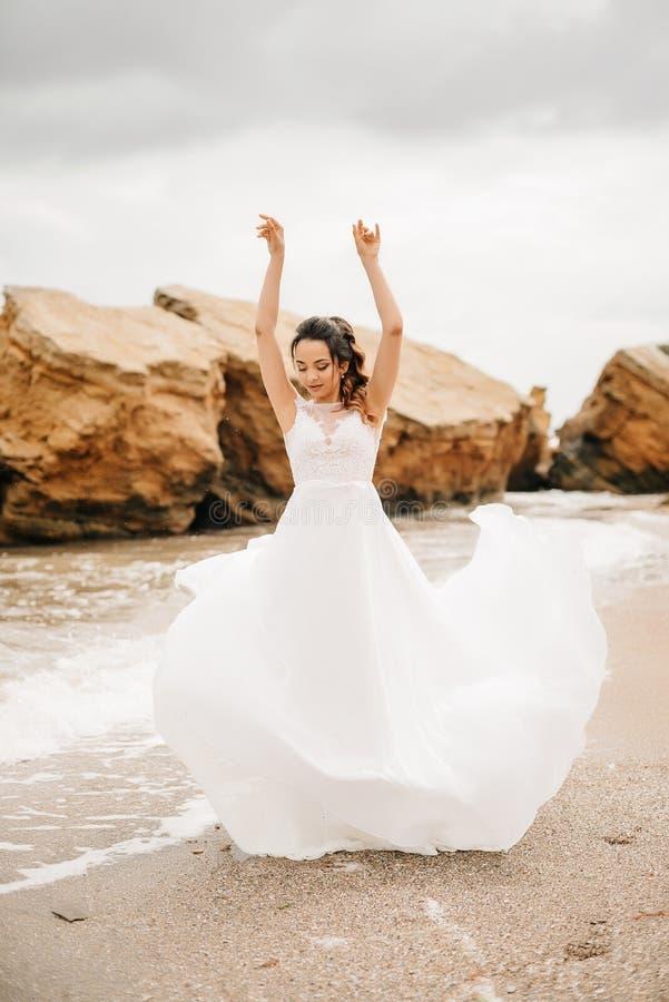 Barnet kopplar ihop brudgummen med bruden på en sandig strand arkivbild