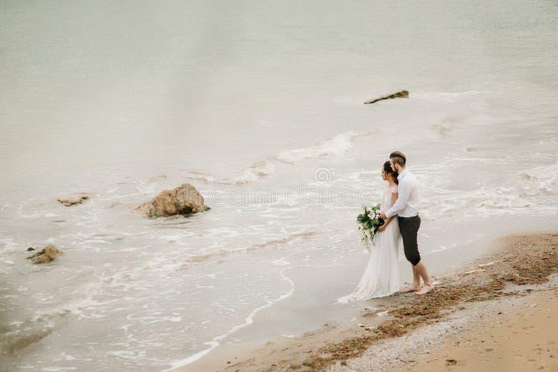 Barnet kopplar ihop brudgummen med bruden på en sandig strand royaltyfri fotografi