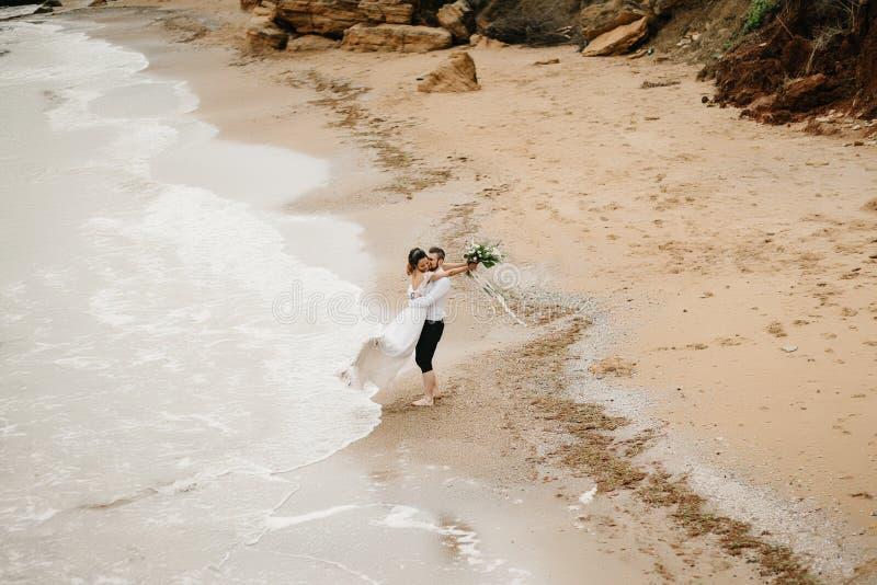 Barnet kopplar ihop brudgummen med bruden på en sandig strand arkivfoto