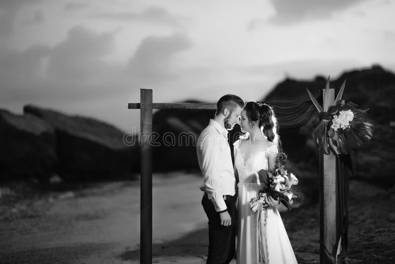 Barnet kopplar ihop brudgummen och bruden med en bukett i aftonen på th arkivfoto