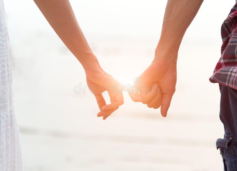 Barnet kopplar ihop den förälskade attraktiva mannen och kvinnan som tycker om romantisk afton på stranden som rymmer att hålla ö royaltyfri bild