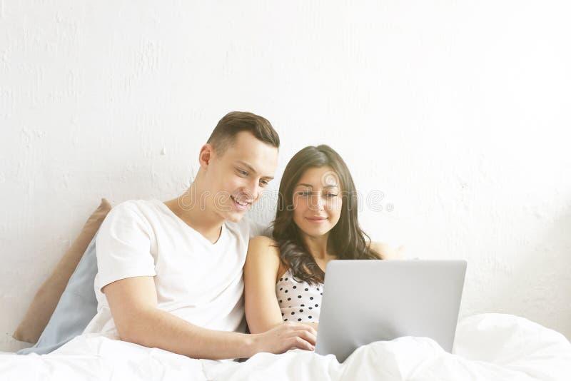 Barnet kopplar ihop den hållande ögonen på TV-program som läser ett meddelande Teknologi- & förhållandebegrepp Moderna romansprob royaltyfri foto