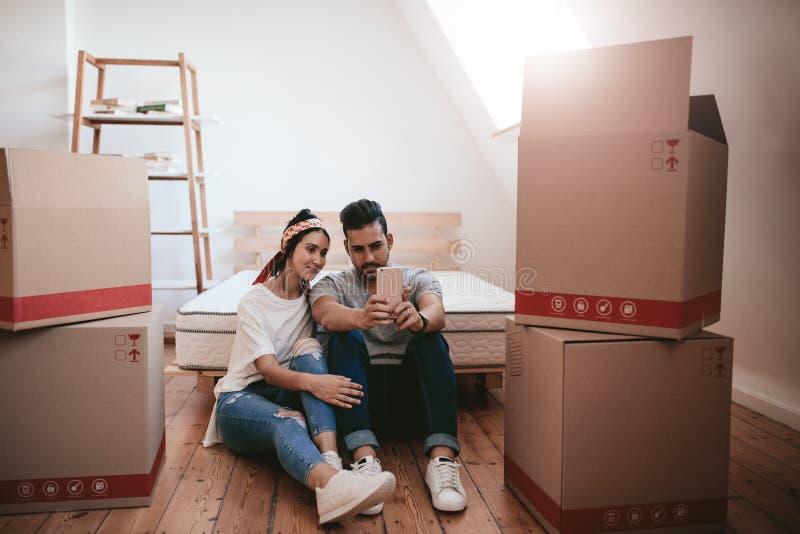 Barnet kopplar ihop det nya hemmet för inflyttningen och taselfie royaltyfri foto
