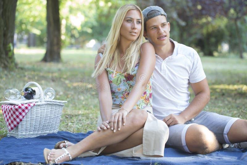 Barnet kopplar ihop förälskat ha en picknick utomhus royaltyfria bilder