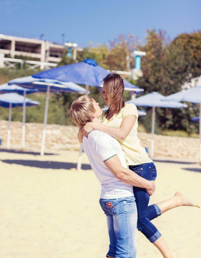 Barnet kopplar ihop förälskat ha gyckel och hoppa på stranden arkivfoton