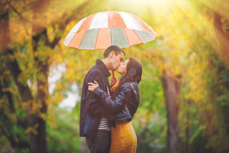 Barnet kopplar ihop förälskat kyssa under paraplyet royaltyfri bild
