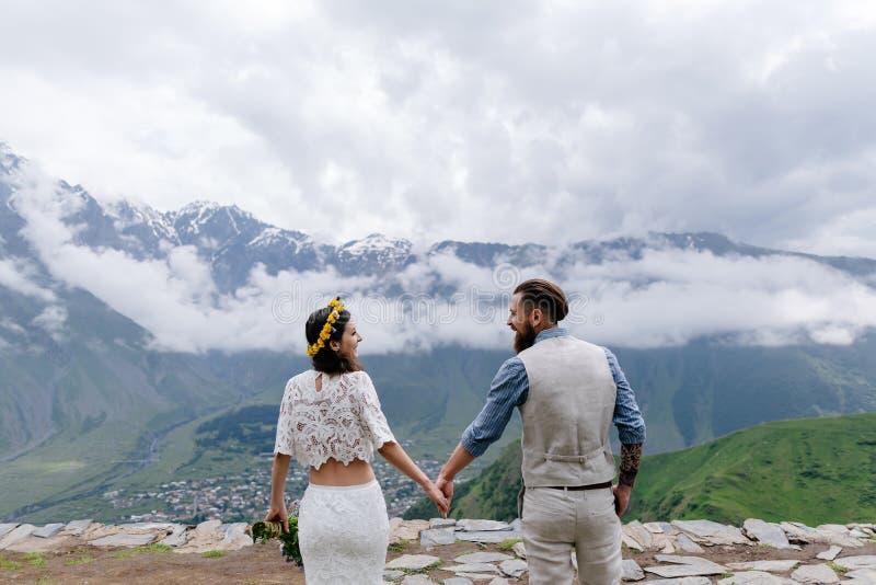 Barnet kopplar ihop förälskat och att se de, en man i en dräkt och flickan i vit med blommor som är stående utomhus arkivbilder