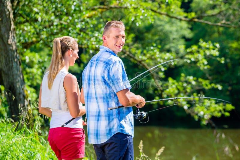 Barnet kopplar ihop fiske eller att meta att stå på flodkust royaltyfria foton