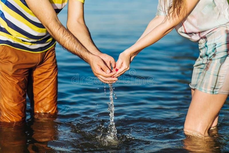 Barnet kopplar ihop flicka- och pojkeinnehavhänder ovanför vattnet royaltyfria bilder
