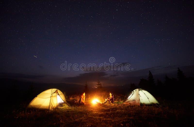 Barnet kopplar ihop fotvandrare som vilar nära det upplysta tältet som campar i berg på natten under stjärnklar himmel royaltyfria foton