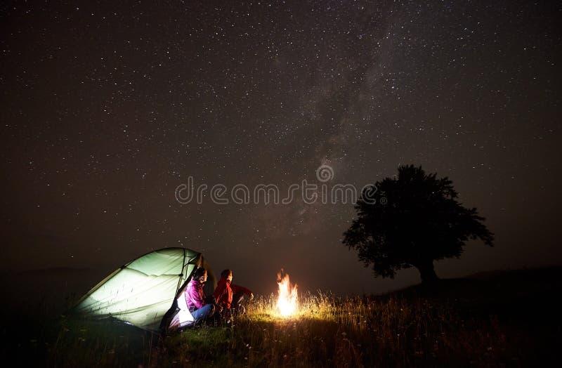 Barnet kopplar ihop fotvandrare som vilar nära det upplysta tältet som campar i berg på natten under stjärnklar himmel royaltyfri fotografi