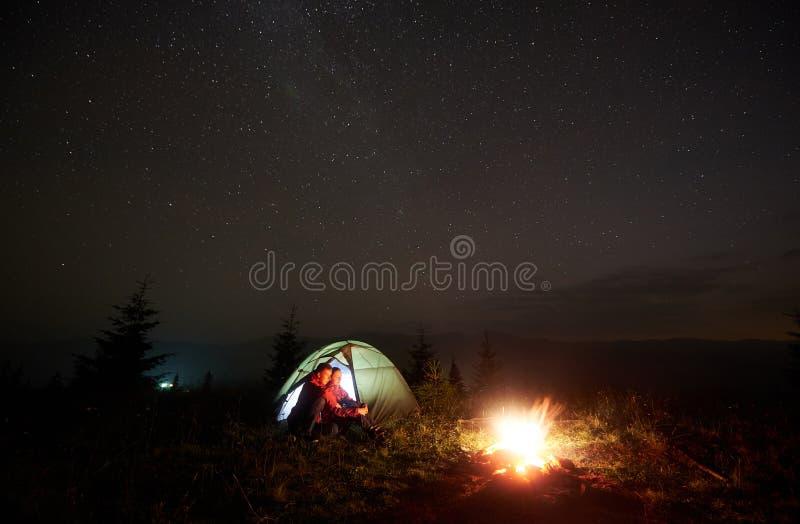 Barnet kopplar ihop fotvandrare som vilar nära det upplysta tältet som campar i berg på natten under stjärnklar himmel royaltyfri bild