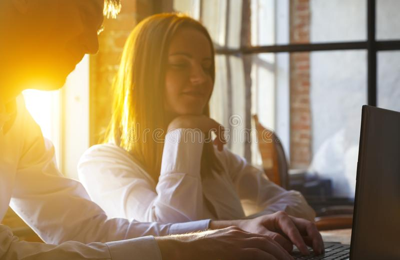 Barnet kopplar ihop genom att använda bärbara datorn på skrivbordet på i ett modernt kontor, vindstil och tänker royaltyfri fotografi