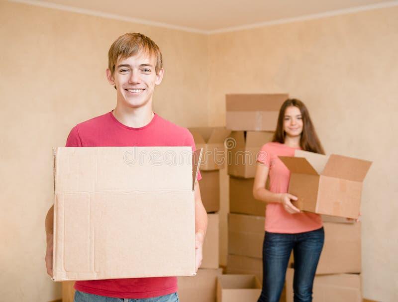 Barnet kopplar ihop hållande kartonger för att flytta sig in i ett nytt hus royaltyfri foto