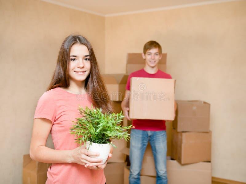 Barnet kopplar ihop hållande kartonger för att flytta sig in i ett nytt hus arkivbilder