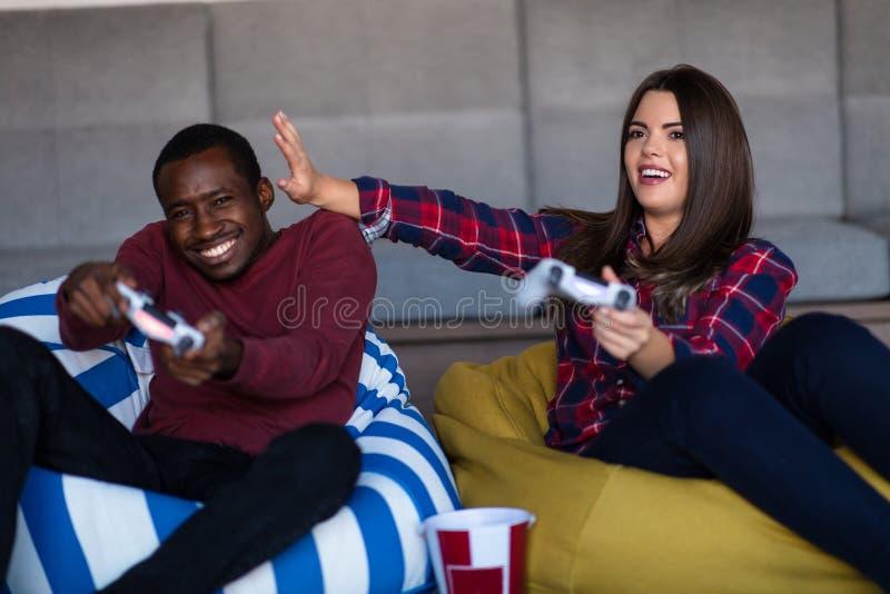 Barnet kopplar ihop hemma att spela videospelet tillsammans royaltyfria bilder