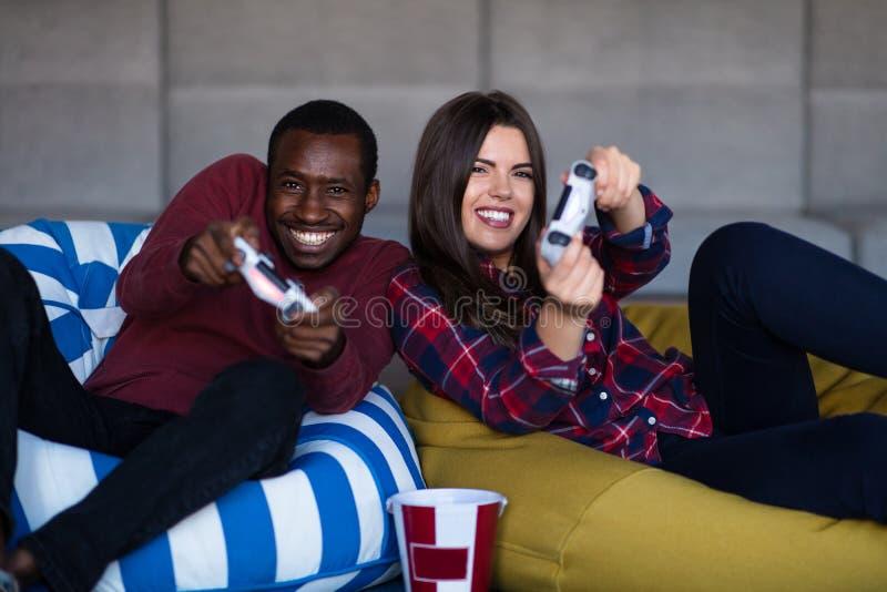 Barnet kopplar ihop hemma att spela videospelet tillsammans arkivfoto