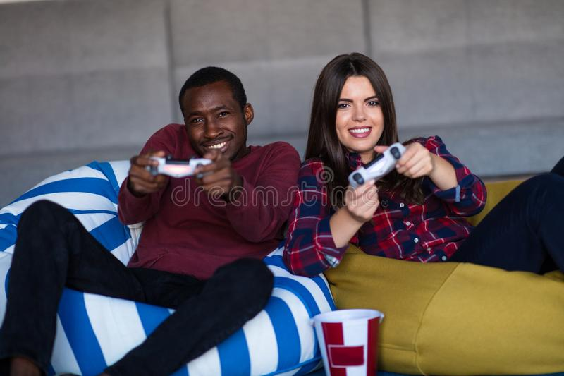 Barnet kopplar ihop hemma att spela videospelet tillsammans arkivbild