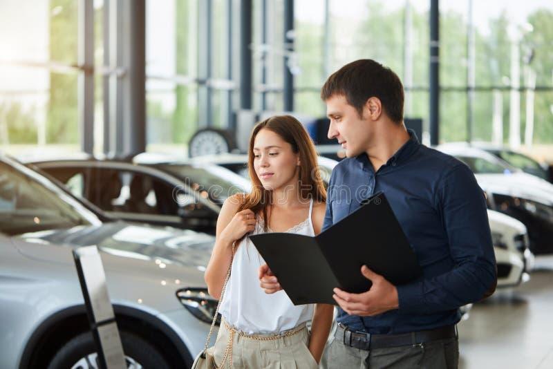 Barnet kopplar ihop i elegant kläder för sommartid väljer en ny bil på bilåterförsäljaren arkivbild