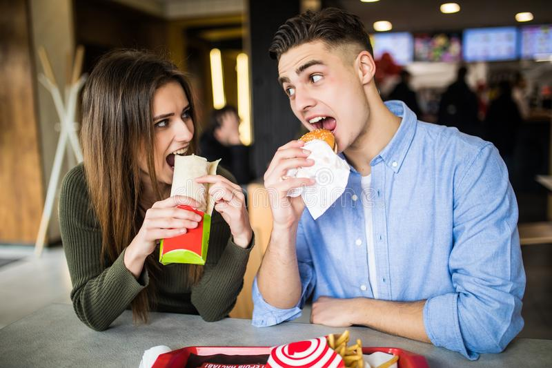 Barnet kopplar ihop i en snabbmatrestaurang som äter hamburgaren och doner arkivfoton