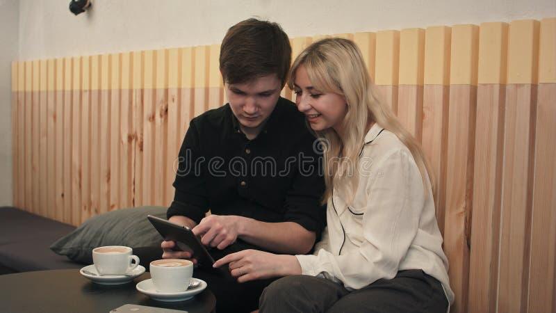 Barnet kopplar ihop i ett kafé som dricker kaffe och använder den digitala minnestavlan arkivfoton