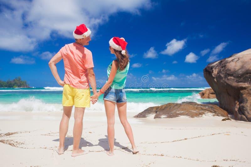 Barnet kopplar ihop i santa hattar som har gyckel på den tropiska stranden nytt år Seychellerna royaltyfri foto