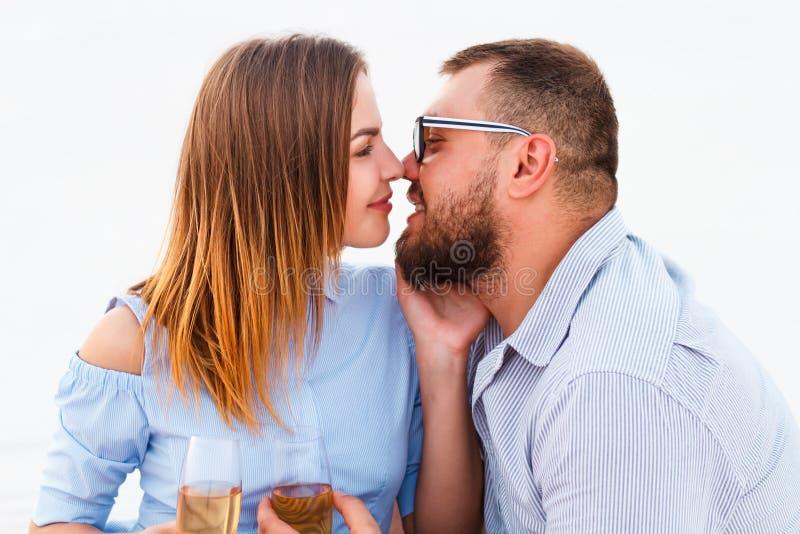 Barnet kopplar ihop kyssande och hållande exponeringsglas i händer, lyckliga par som tycker om picknicken på stranden och, har br royaltyfria bilder