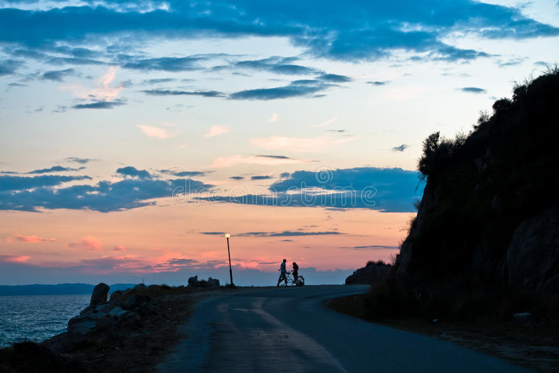 Barnet kopplar ihop med den tandema cykeln på havskusten efter solnedgång arkivbilder