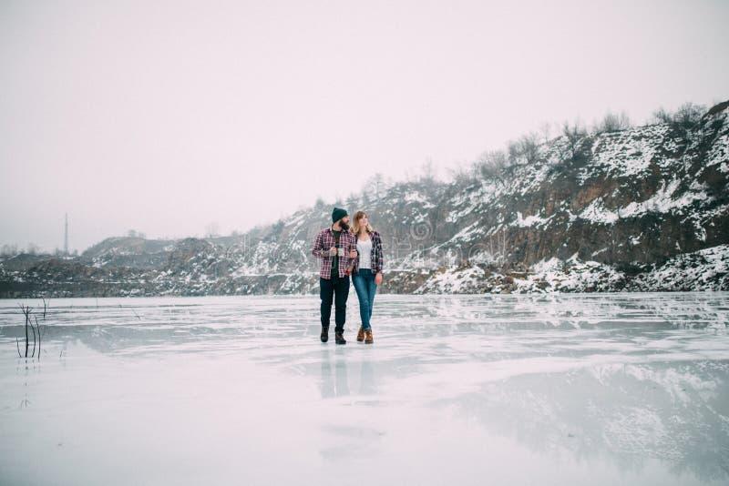 Barnet kopplar ihop med rånar av te går på is av den djupfrysta sjön royaltyfri fotografi