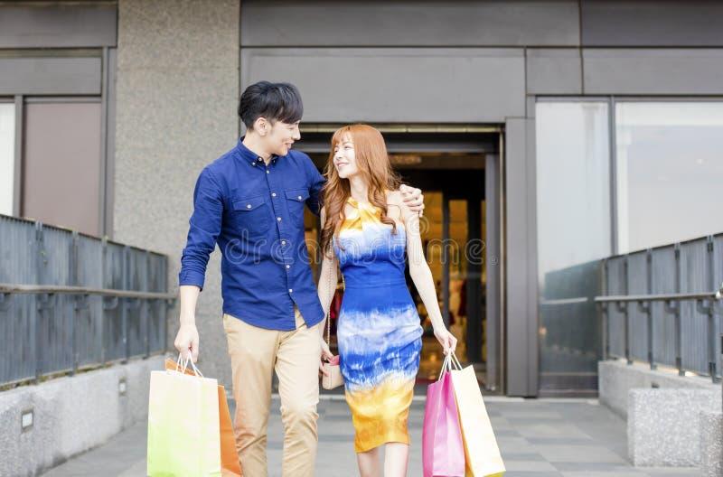 Barnet kopplar ihop med shoppingpåsar som går i galleria arkivbild